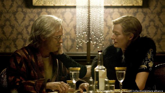 Brad Pitt as an old man sits at a dinner table with Tilda Swinton, dressed in a fur scarf in a still from the film 'The Curious Case of Benjamin Button' (Paramount/Courtesy Everett Collection/picture alliance )