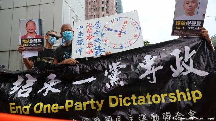 Pro-democracy activists in Hong Kong hold a banner reading End One-Party Dictatorship