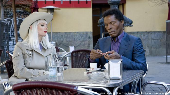 Swinton in a cowboy hat with blonde hair sitting next to actor Isaach De Bankrole in a still from the film 'The Limits of Control' (Focus Features/Courtesy Everett Collection/picture alliance)
