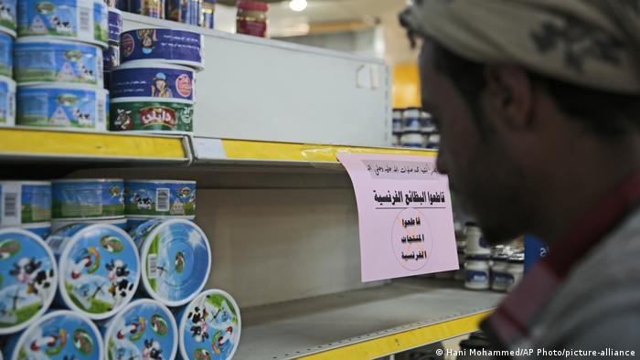 A man shops next to a notice calling for a boycott of French products at a supermarket in Sanaa, Yemen