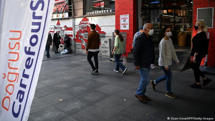 People wearing face mask walk in front of a French supermarket Carrefour in Istanbul