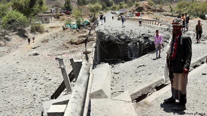 Men standing amid rubble in Yemen
