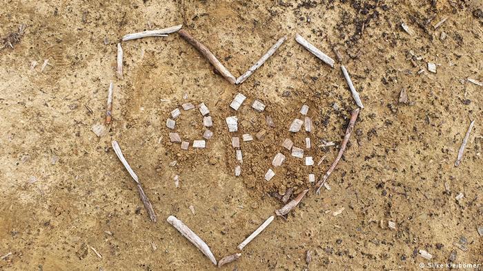 Auf heller Erde ist ein Herz aus Rindenstücken gelegt. In der Mitte ist das Wort Opa zu lesen. Tod und Trauer in der Corona-Zeit