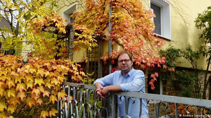 Ein Mann lehnt sich auf ein eisernes Tor, neben und hinter ihm ist rot-gelbes Herbstlaub vor einer gelben Hauswand zu sehen. Tod und Trauer in der Corona-Zeit