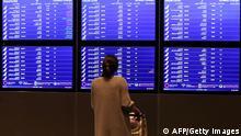 سيدة تتفقد برنامج إقلاع وهبوط الطائرات في مطار حمد الدولي بالدوحة
