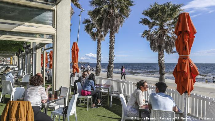 Diners are seen at a restaurant looking out towards St. Kilda Beach