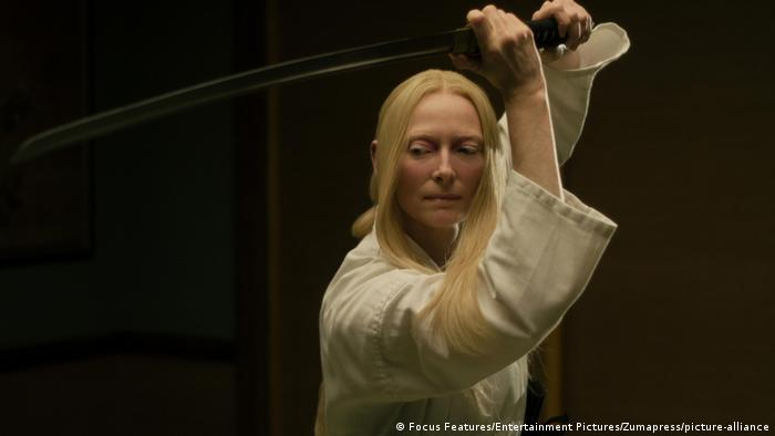 Tilda Swinton wearing white and holding a sword in the air (Focus Features/Entertainment Pictures/Zumapress/picture-alliance)