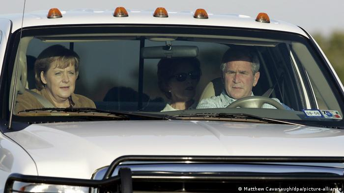 Merkel and Bush in a pickup truck (Matthew Cavanaugh/dpa/picture-alliance)