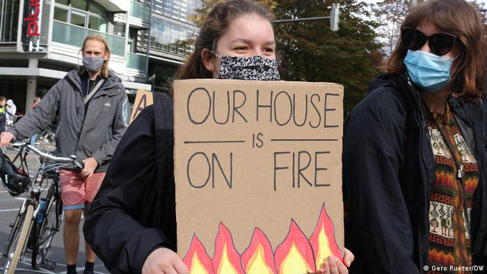 A woman wearing a face mask holds up a poster reading Our house is on fire