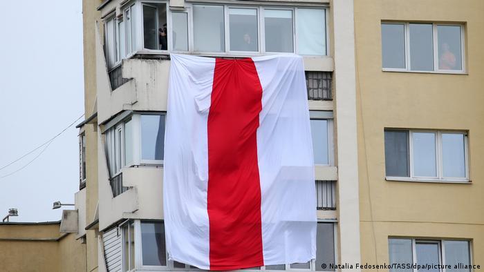 Бело-красно-белый флаг на балконе в многоэтажном доме