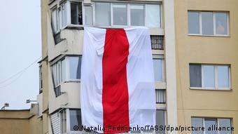 Бело-красно-белый флаг на здании одного из домов в Минске, 27 октября 2020 года