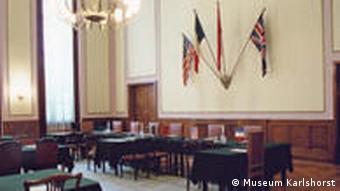 Der Kapitulationsaal im Museum Karlshorst in Berlin. Hier unterzeichnete Generalfeldmarschall Wilhelm Keitel die Kapitulationsurkunde. Hinter der Tisch- und Stuhlreihe hängen die Fahnen der Alliierten: USA, Frankreich, Sowjetunion und Großbritannien. (Foto: Museum Karlshorst)
