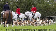Drei Männer auf Pferden umgeben von vielen Hunden (Ashley Cooper/Global Warming Images/picture alliance)