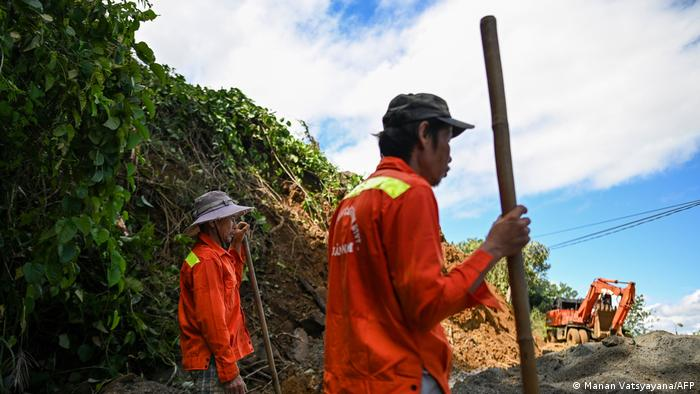 Workers clear debris from a landslide that blocked a road