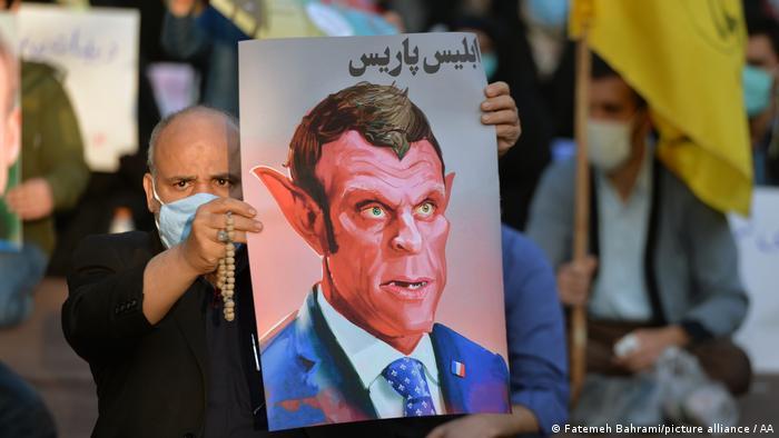 Карикатура на президента Франции Эмманюэля Макрона в руках участника акции протеста в Тегеране 28 октября 2020 года