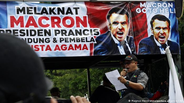 A man in Indonesia stands in front of a banner protesting Macron and speaks into a microphone