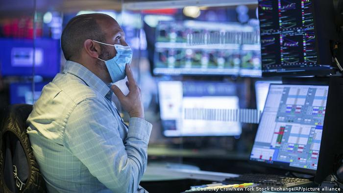 A man wears a mask as he works at his post on the trading floor of the New York Stock Exchange