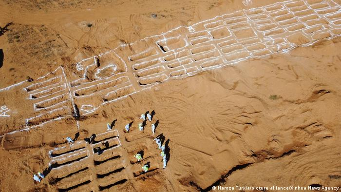 Workers of the General Authority for Research and Identification of Missing Persons in Libya are seen on the site of mass graves in Tarhuna, Libya