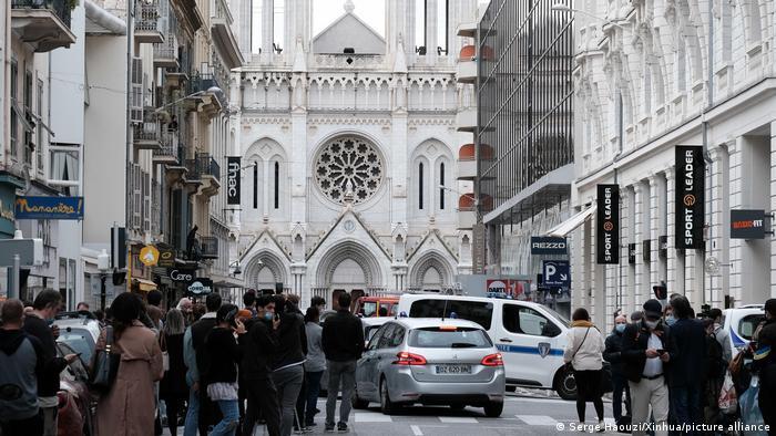 Pessoas nas ruas de Nice, com basílica ao fundo