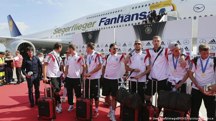 The German national football team arriving at the airport, posing together on a red carpet in front of their plane (Uwe Kraft / imageBROKER / picture alliance)