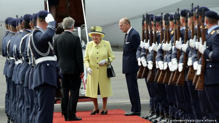 Queen Elizabeth II and Prince Philip arriving in Tegel on a red carpet with soldiers lined up to greet (Jörg Carstensen / dpa / picture alliance)