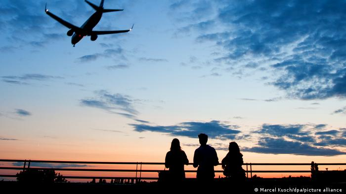 Three silhouettes of people watching the sunset seen from the airport (Marcel Kusch / dpa / picture alliance)