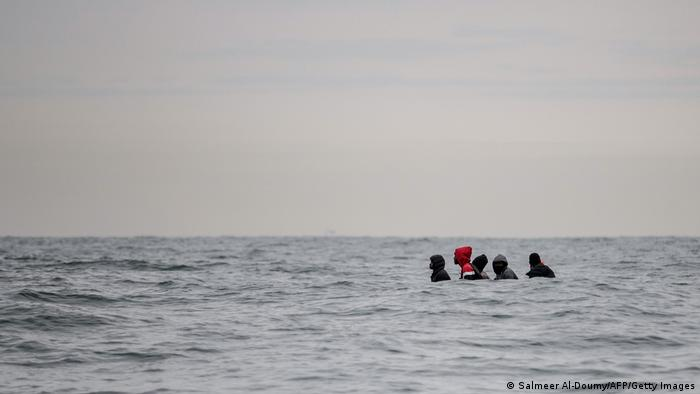 Migrants sit in a boat navigating the waters in the English Channel off the coast of northern France
