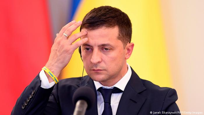 Volodymyr Zelenskiy touches his forehead during a press conference in 2019