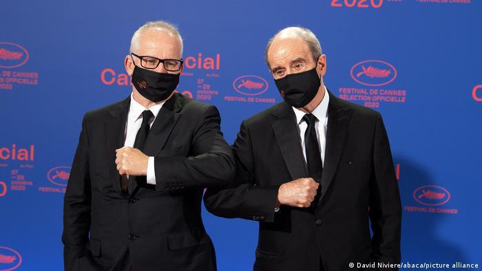 Zwei Männer in Smoking und schwarzer Masken begrüßen sich mit den Ellenbogen (Foto: David Niviere/abaca/picture alliance).