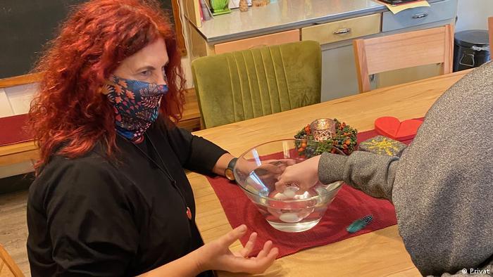 Trauerbegleiterin Mechthild Schroeter-Rupieper sitzt mit Mund-Nasen-Schutz am Tisch, auf dem eine Schüssel mit Wasser steht. Die Hand eines Jugendlichen drückt einen Tischtennisball ins Wasser