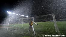 A worker disinfects the goal net at half-time of the closed-door Copa Sudamericana second round football match between Brazil's Vasco da Gama and Venezuela's Caracas at the Sao Januario stadium in Rio de Janeiro, Brazil, on October 28, 2020, amid the COVID-19 novel coronavirus pandemic. (Photo by MAURO PIMENTEL / various sources / AFP)