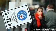 Pedestrians walk along a sign that reminds to wear a face mask as the coronavirus disease (COVID-19) outbreak continues in Frankfurt, Germany