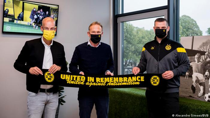 Borussia Dortmund's Daniel Lörcher (right) with club bosses Hans-Joachim Watzke and Carsten Cramer holding ribbon saying: 'United in Remembrance' and 'United against Antisemitism'