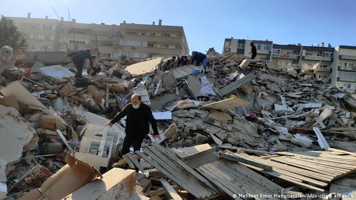 A man walks among debris of collapsed buildings in Izmir, Turkey following an earthquake