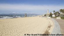 23.10.2020, Spanien, Palma de Mallorca: Ein Bademeister (l) arbeitet am leeren Strand von Palma. Von Herbstferien ist auf Mallorca kaum etwas zu sehen. Die meisten Hotels sind zu, der Strand ist leer. (zu dpa «Geisterinsel» Mallorca blickt mit Neid und Hoffnung auf die Kanaren) Foto: Mar Granel Palou/dpa   Verwendung weltweit