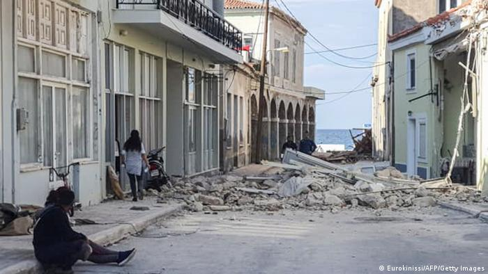 People walk past a destroyed house after an earthquake in the island of Samos (Eurokinissi/AFP/Getty Images)