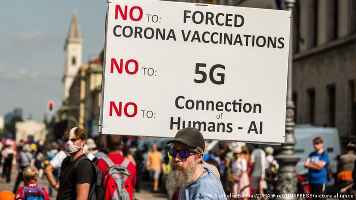 A protester in Munich holds a banner against vaccines and 5G