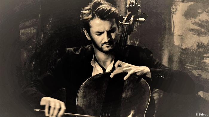 A photo of Mounir Mahmalat playing the cello in black and white