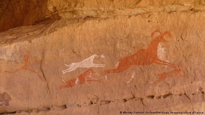Felsmalerei eines Jägers und seiner Hunde, die eine Ziege oder Antilope verfolgen