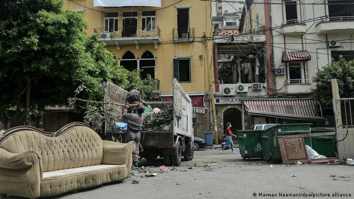 Debris is scattered on a residential street, including a large sofa. A man picks up garbage and puts it in a truck
