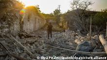 An Armenian soldier stands among the ruins of a house destroyed by a recent shelling in Martakert