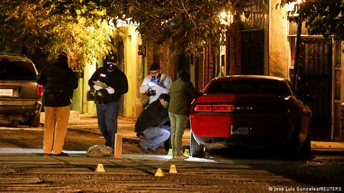 Forensic technicians work at a crime scene where unknown assailants gunned down Multimedios Channel 6 news anchor Arturo Alba
