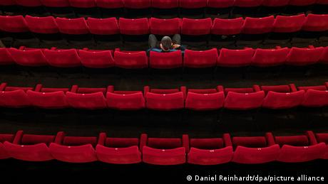 Person sits all alone in a movie mtheater, rows of red seats