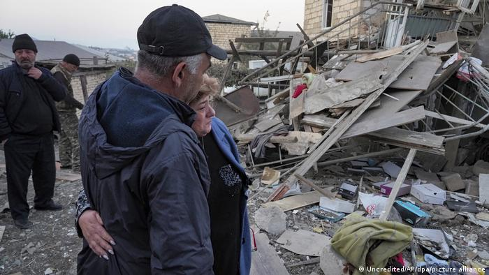 People in Stepanakert look at the rubble of a destroyed building