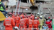 Rescue workers try to rescue residents trapped in debris of a collapsed building, in Izmir, Turkey, Saturday, Oct. 31, 2020. Rescue teams on Saturday plowed through concrete blocs and debris of eight collapsed buildings in search of survivors of a powerful earthquake that struck Turkey's Aegean coast and north of the Greek island of Samos. (AP Photo/Ismail Gokmen)