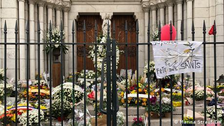 Muitas flores em frente à igreja. Há um portão, que está fechado. No portão, está pendurado com cartaz com uma frase em francês e o desenho de uma pomba.