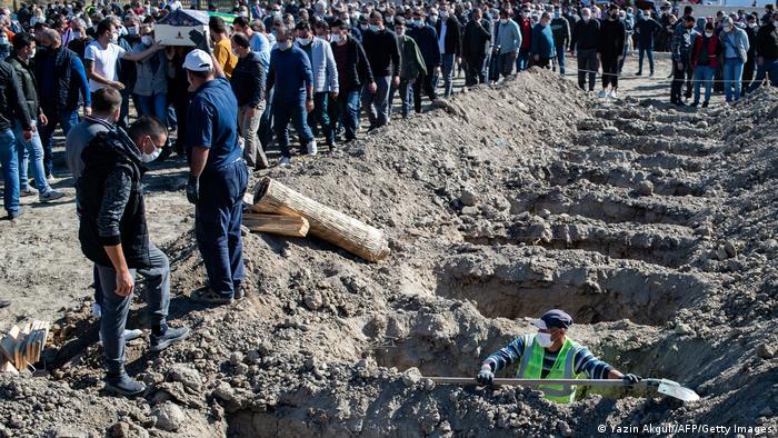 Ein Mann hebt eine Reihe Gräber aus, im Hintergrund begleitet eine Menschenmenge einen Sarg (Yazin Akgul//AFP/Getty Images)