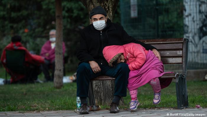 Ein Mann sitzt auf einer Parkbank, ein Kind legt seinen Kopf auf seinen Schoß (Burak Kara/Getty Images)