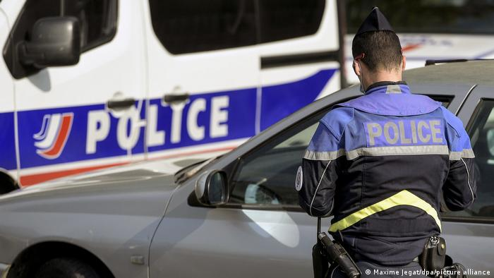 A French policeman in front of a car