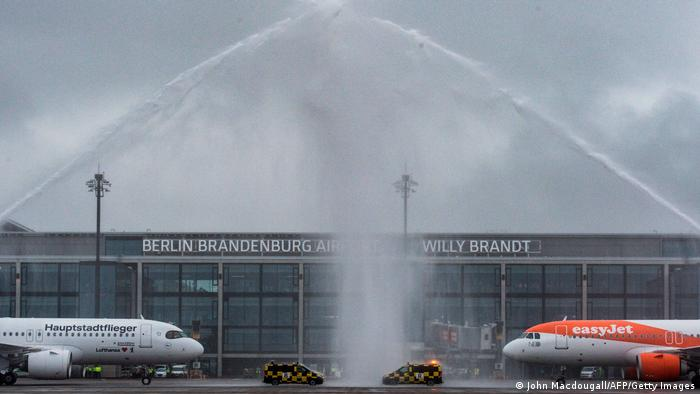 Fire engines spray water to greet the arrival of EasyJet and Lufthansa planes at Berlin's new airport